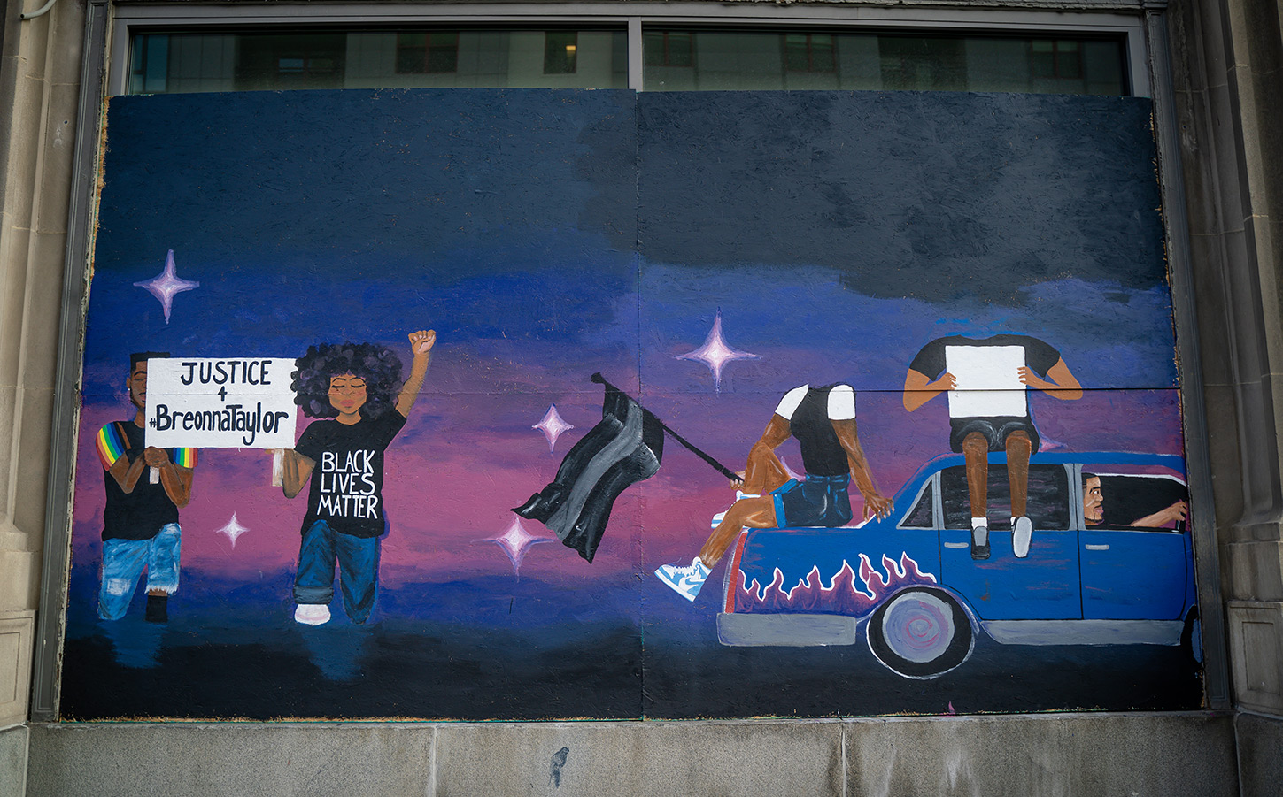 "A color photo that is taken front-on. The picture is of street art painted on plywood covering windows on a building downtown Columbus. The background of the art is a top-to-bottom gradient: black, blue, pink, purple, blue, black. The bottom right corner shows two figures holding a sign that reads ""Justice for Breonna Taylor."" The bottom right corner shows a blue car with pink and purple flames. Two headless figures sit on the car, third figure is driving the car in the rightward direction."