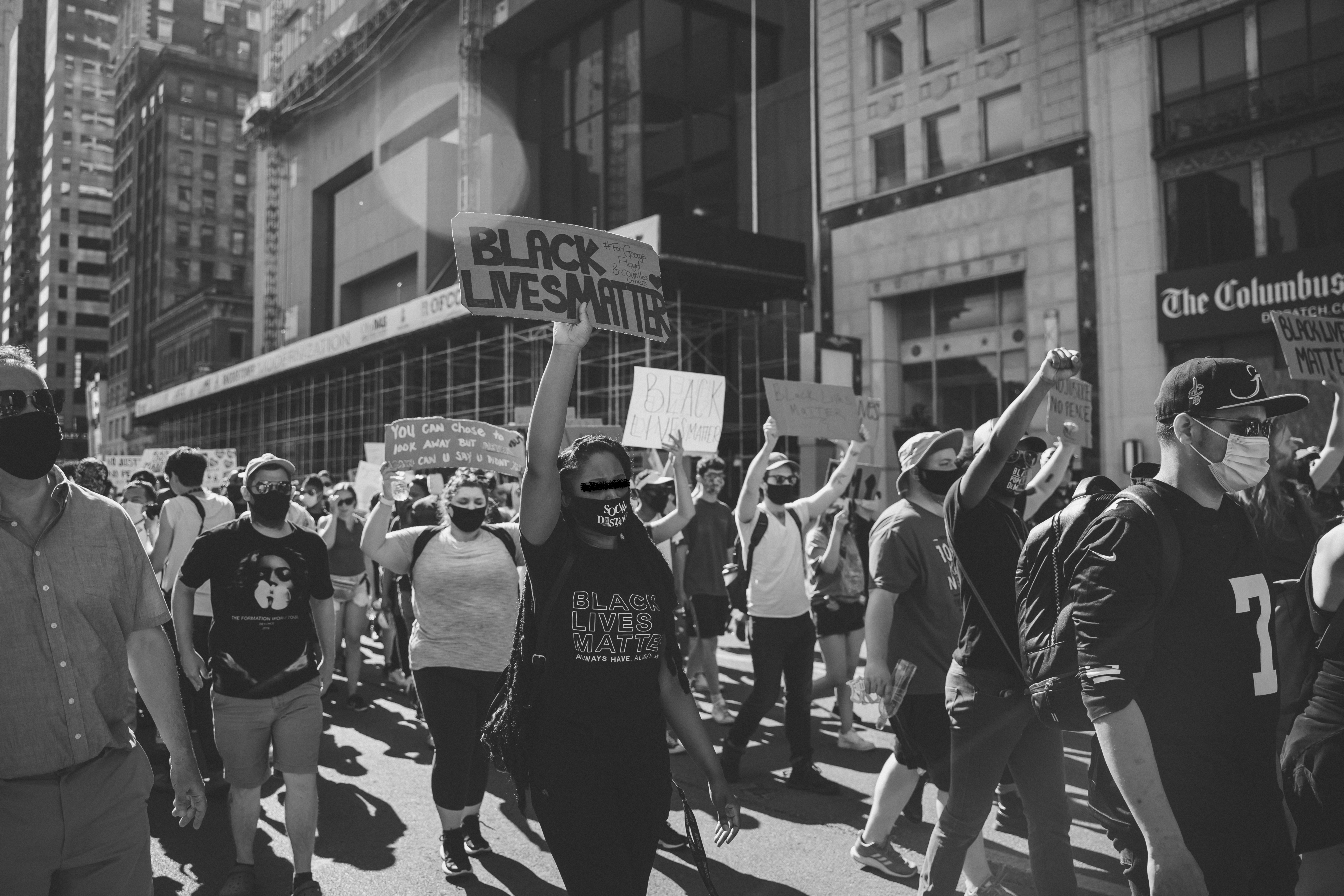 "A black and white photograph with the bottom half of the frame fill of protestors demonstrating by walking from right to left, while raising their closed fists and holding signs. The focus predominantly lands on one protestor in the middle holding a sign and wearing a shirt that reads ""Black Lives Matter."""