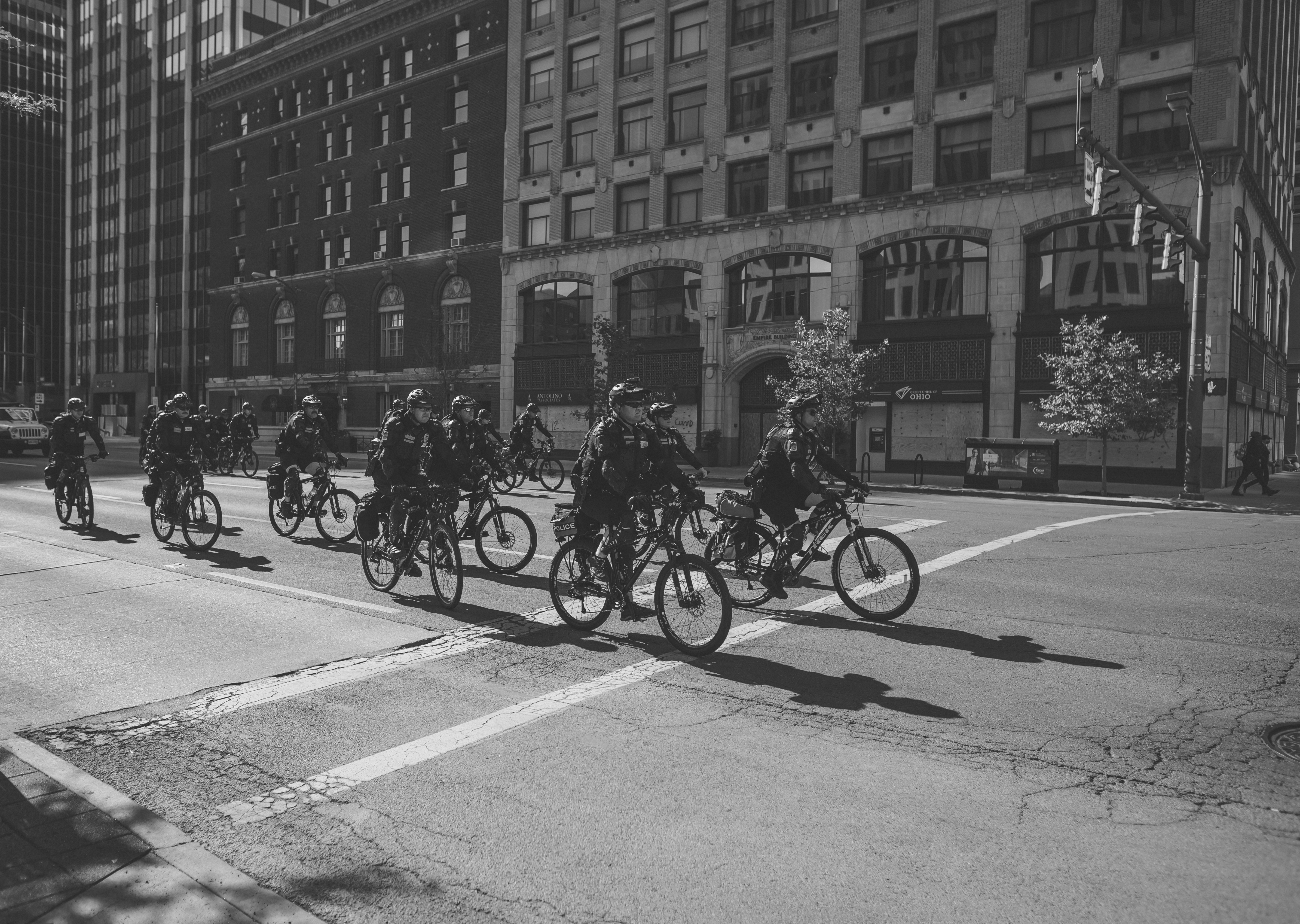 A black and white photograph. More than fifteen police officers on bicycles ride in the street from the right side of the frame and into the middle of the frame. They ride in three columns of about 5 officers. The background of the image shows buildings and the oncoming intersection.