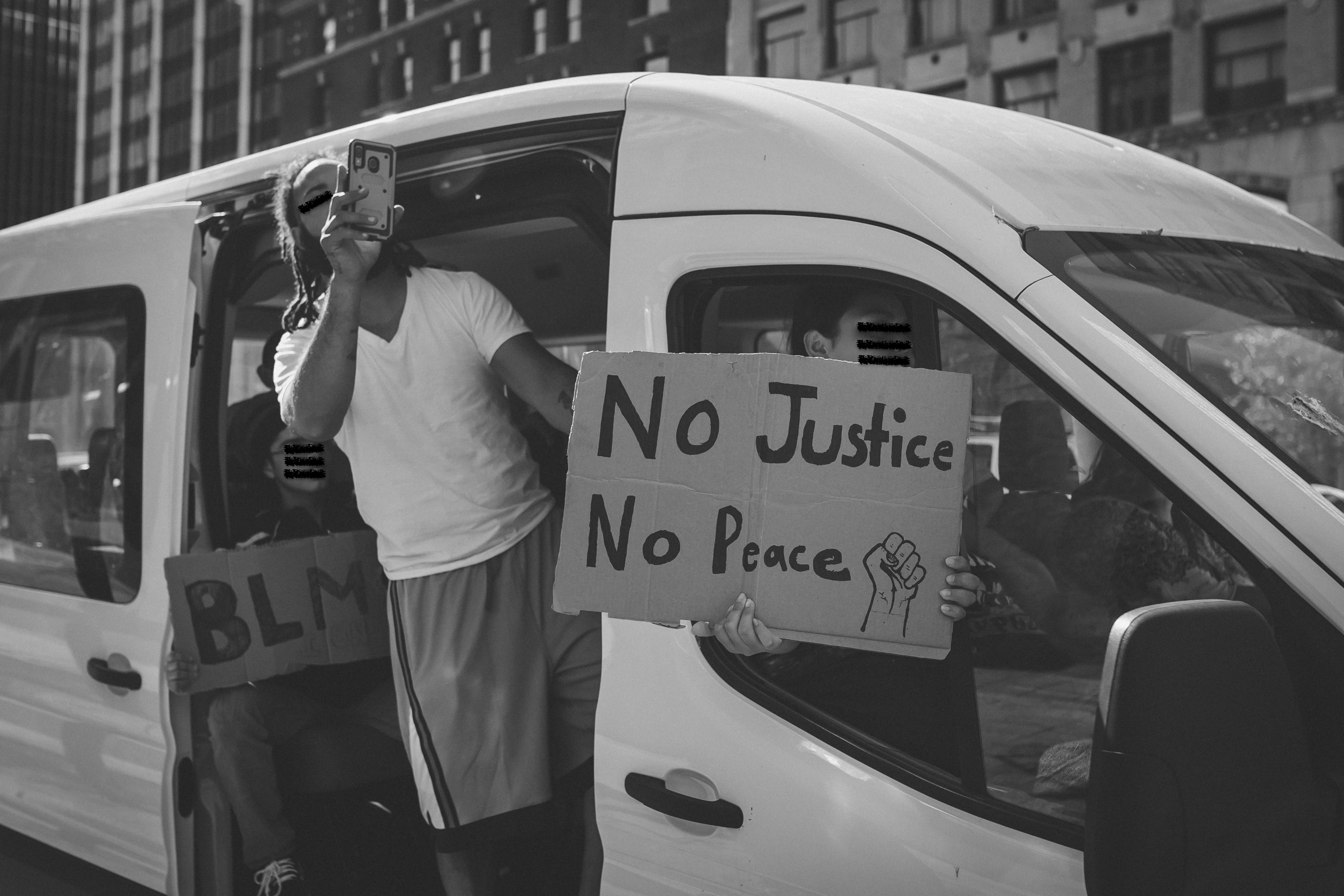 "A black and white photo that fills the majority of the frame with protestors in a white van, shown from the passenger side. The van door is slid back and a protestor leans out of the door and holds up a phone to record. The shot-gun seat has a protestor that holds a sign out the window that covers their face and reads "" No Justice, No Peace"" with the image of a closed fist. In the back of the van, a third protestor sits and hold a sign that reads ""BLM."""