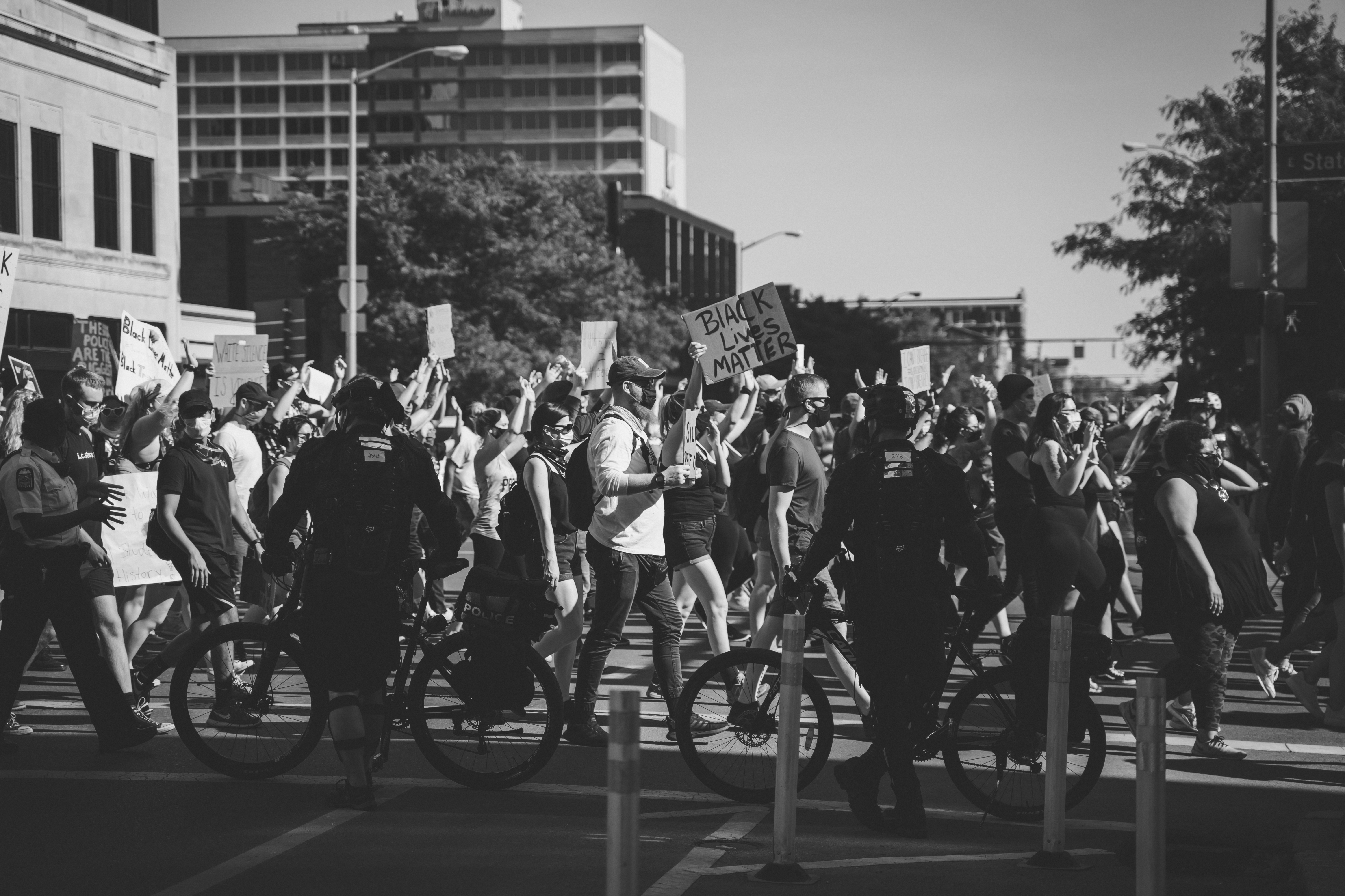 Black and white photograph shows Black Lives Matter protesters walking in one direction (from left to right) and consuming the bottom of half of the image, some of them raise signs. Between the viewer and the protestors are two police officers standing next to their bicycles with their backs turned to the viewer. The top half of the fame shows the sky, trees, and the tops of buildings.