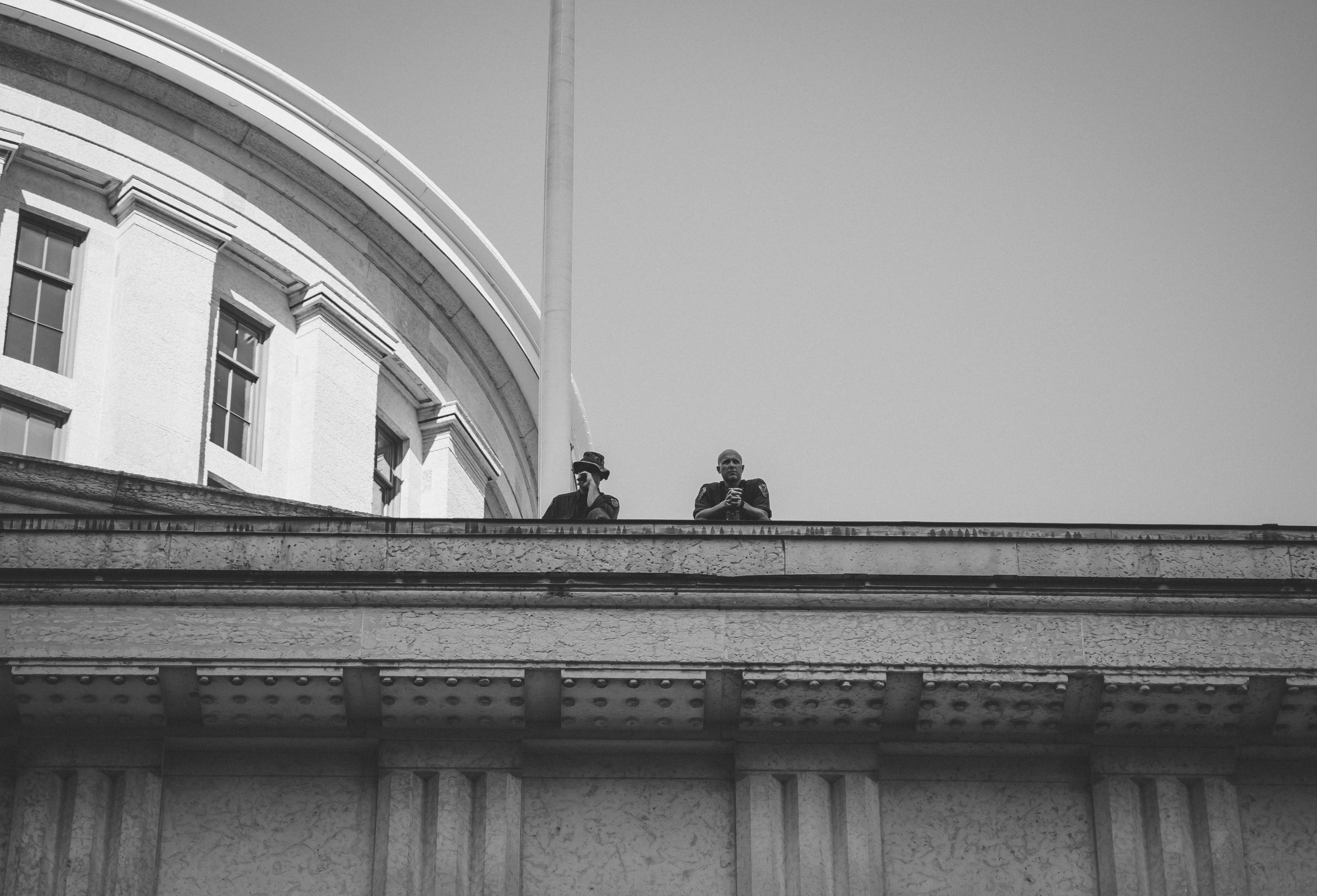 A black and white photo. In the middle of the image are two police offers overlooking BLM protests at the Ohio Statehouse. The viewer stands beneath them and sees the officers from the elbows up. The top right corner os the frame shows the dome of the Statehouse and the reminder of the top half shows and even gray-toned sky.