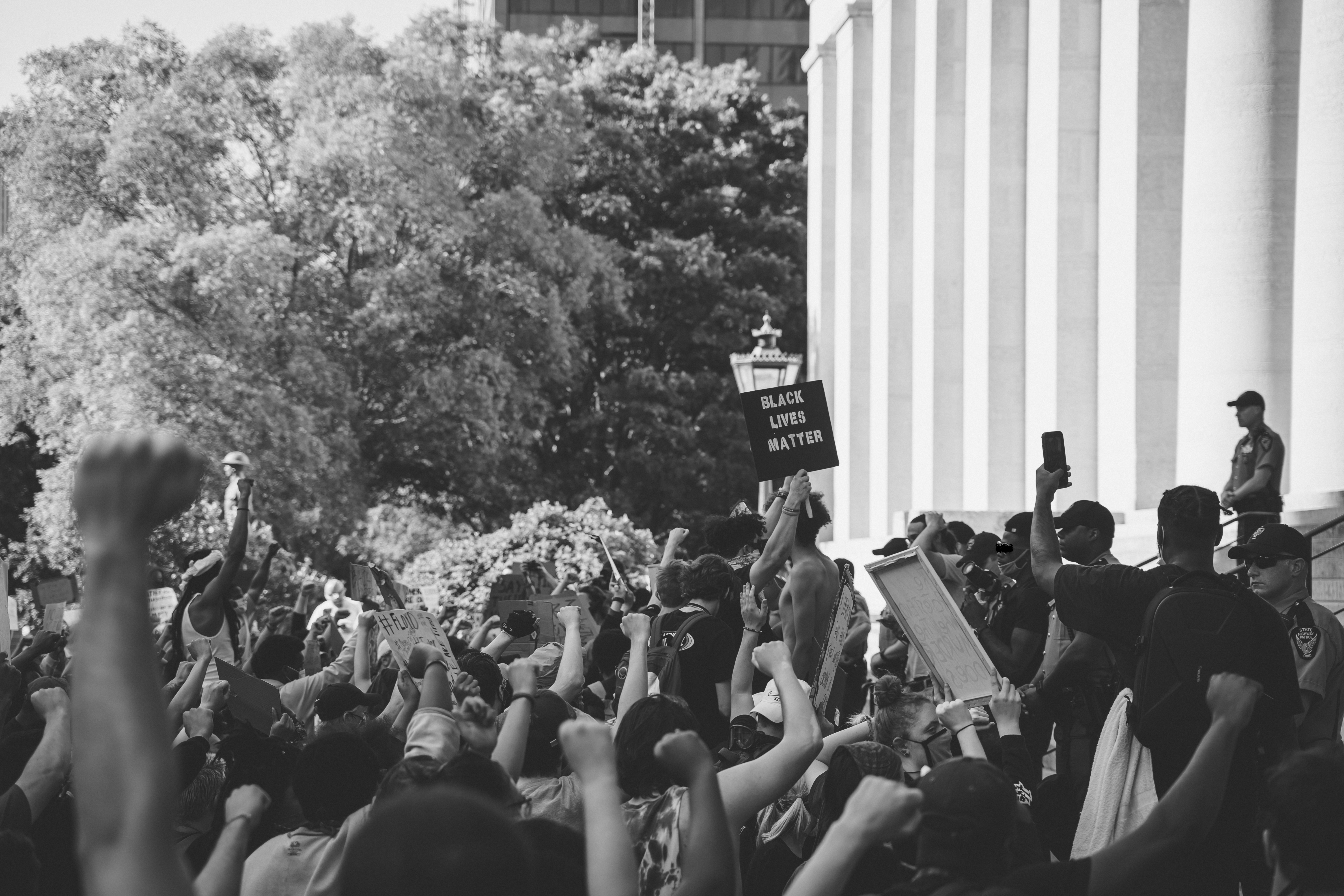 "Black and white photo shows BLM protestors at Ohio State house. The viewer stands behind the protestors on their right-hand side. Majority of the protestors have bare arms and raised closed fists or signs and fill the bottom third of the image. There is one readable sign: ""Black Lives Matter."" The pillars of the state house fill the right half of the image above the protestors. The top left half of the image shows leafy trees."