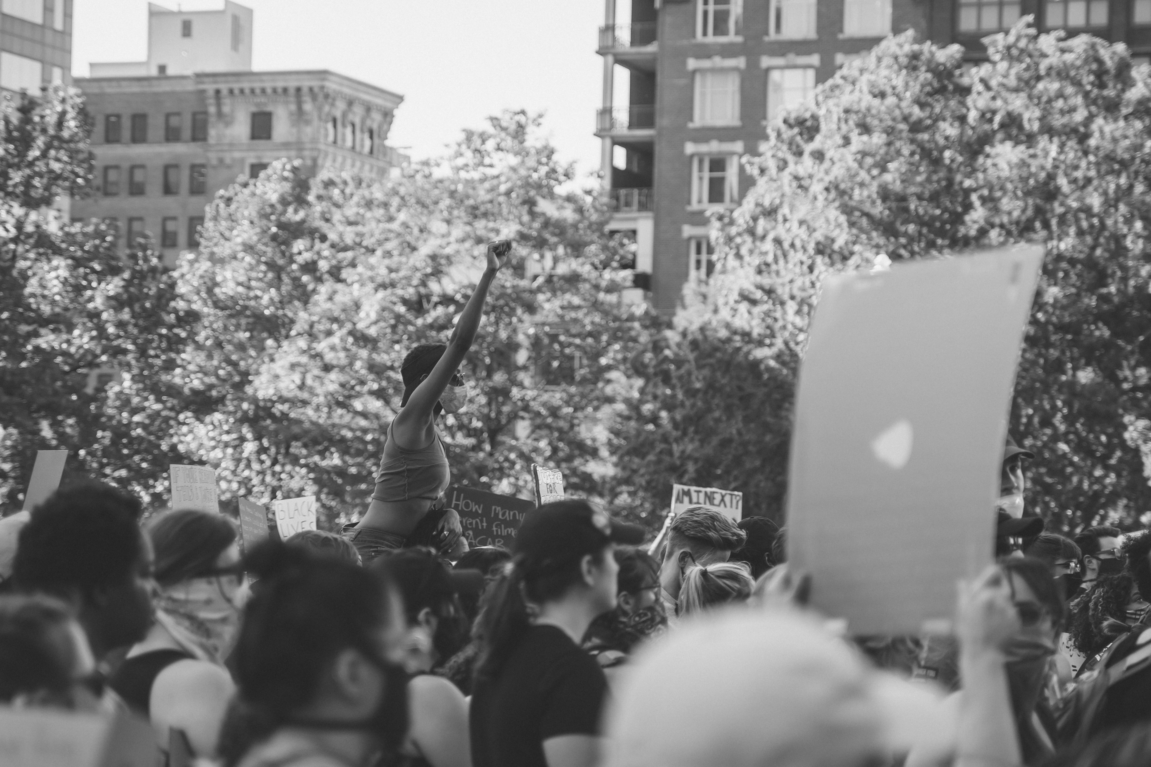 The middle ground of the black and white photo is in focus and shows a protestor during black lives matter demonstration sitting on someone's shoulders and is raising their closed right fist. The foreground shows blurred protestors facing the right side of the photo, with some holding signs. The background shows trees and buildings.