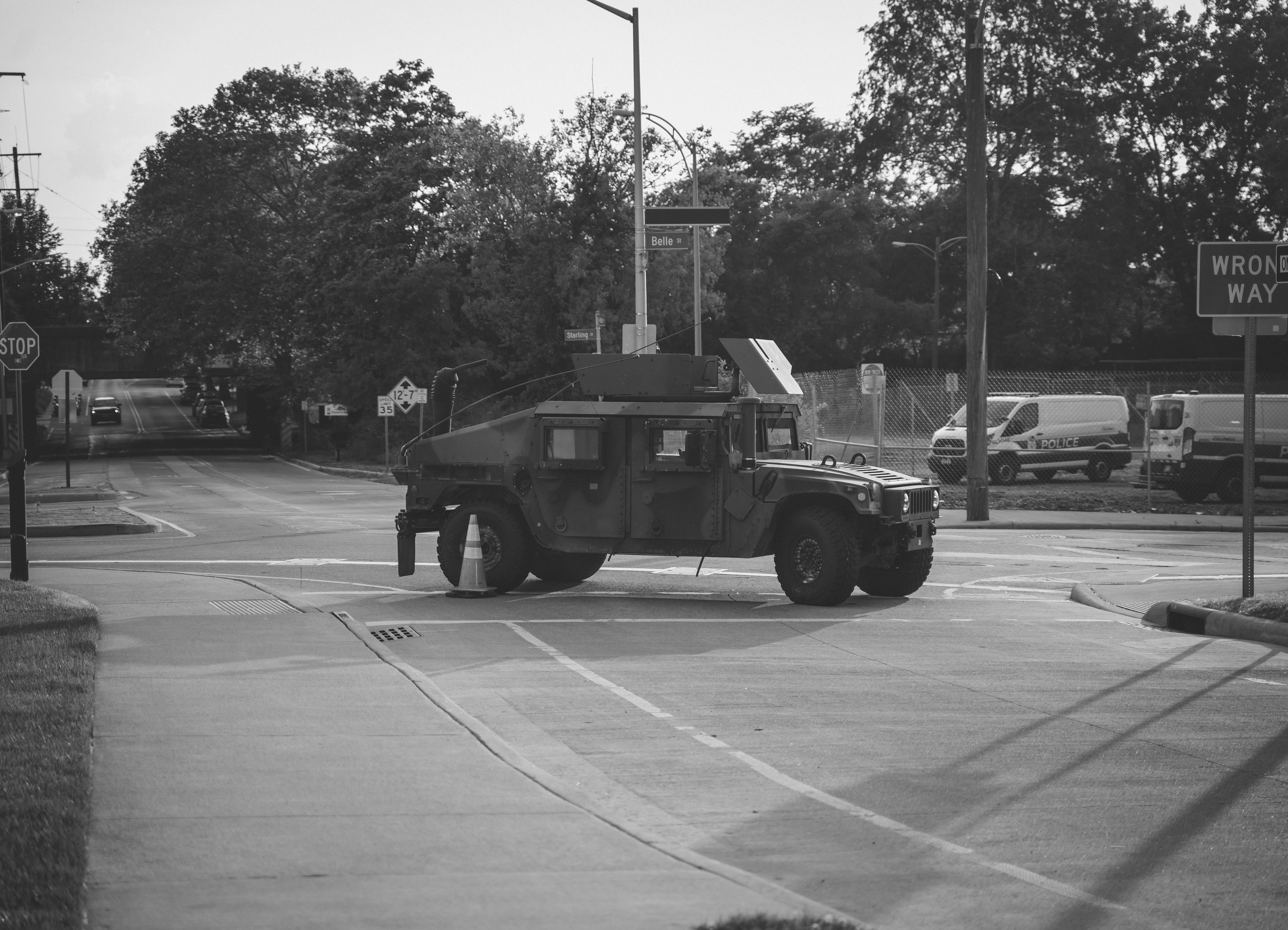 "A black and white photograph. The center of the frame is a military vehicle in downtown Columbus during BLM protests and blocks off an intersection. The background features police vehicles, streetlights and four roads that meet at the intersection the military vehicle sits in. On the right edge of the image, a street sign that is cut off a bit reads ""Wrong Way."""