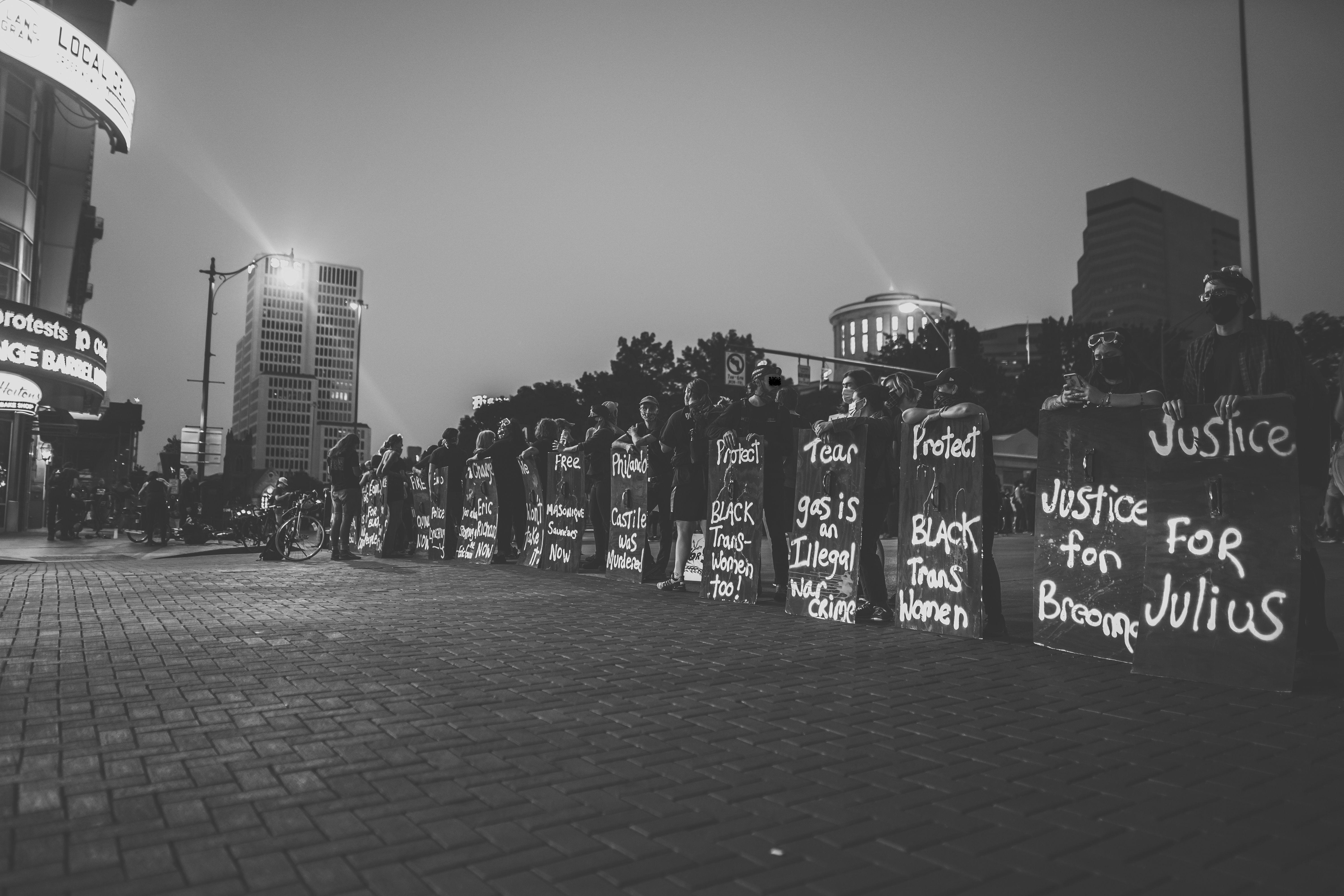 "A black and white photograph that shows BLM protesters lined up from the bottom right corner of the image and receding into the background in the middle of the frame. The protestors stand behind signs that reach chest-height in downtown Columbus. Some read: ""Justice for Julius,"" ""Protect Black Trans Women,"" or ""Tear gas is an Illegal war crime."""