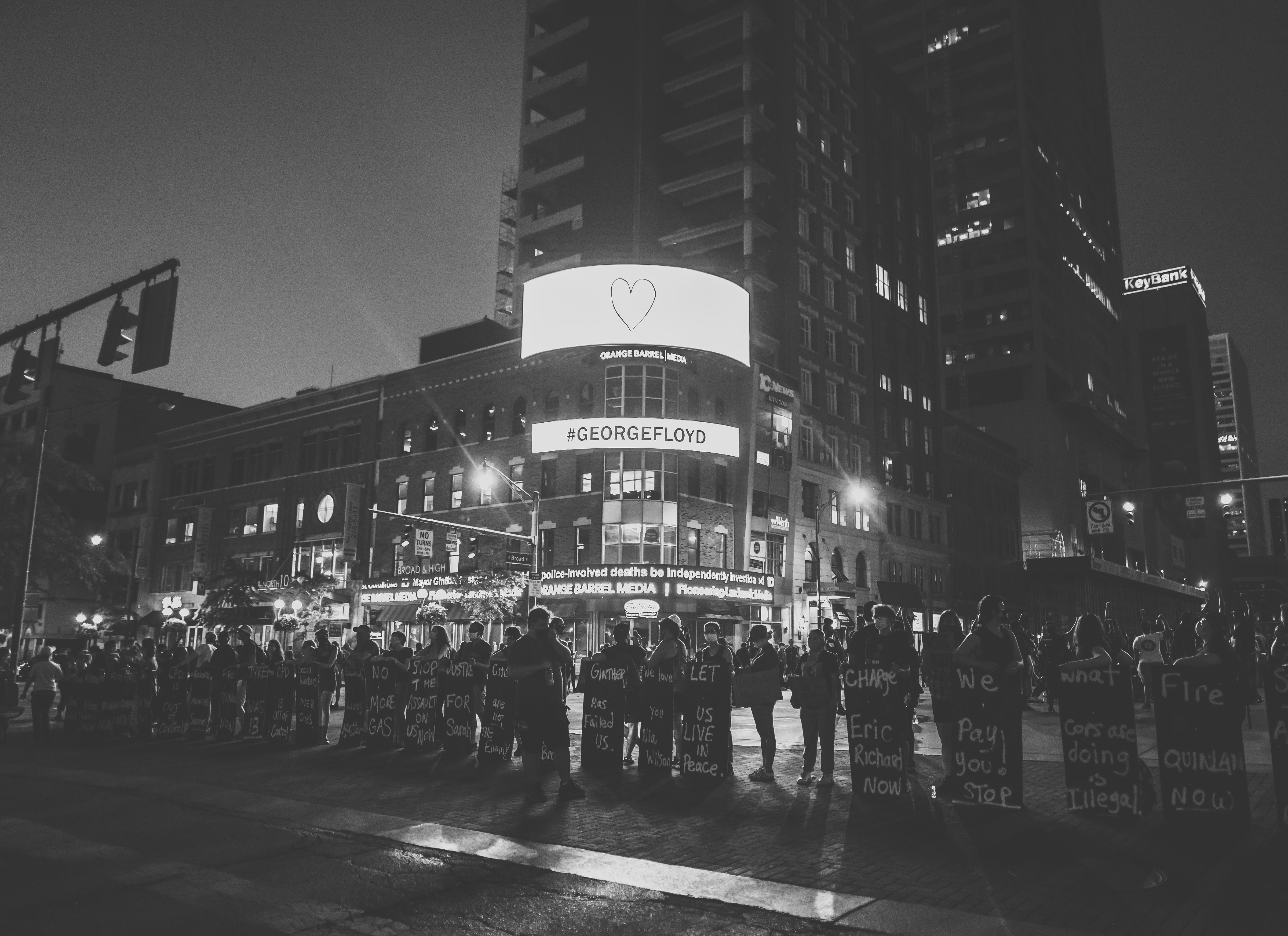 "A black and white photograph. In a line across the bottom third of the image stand lines up BLM protesters that are holding chest-high signs in downtown Columbus at night. The background shows a building with a LED screen that reads ""#GeorgeFloyd."""