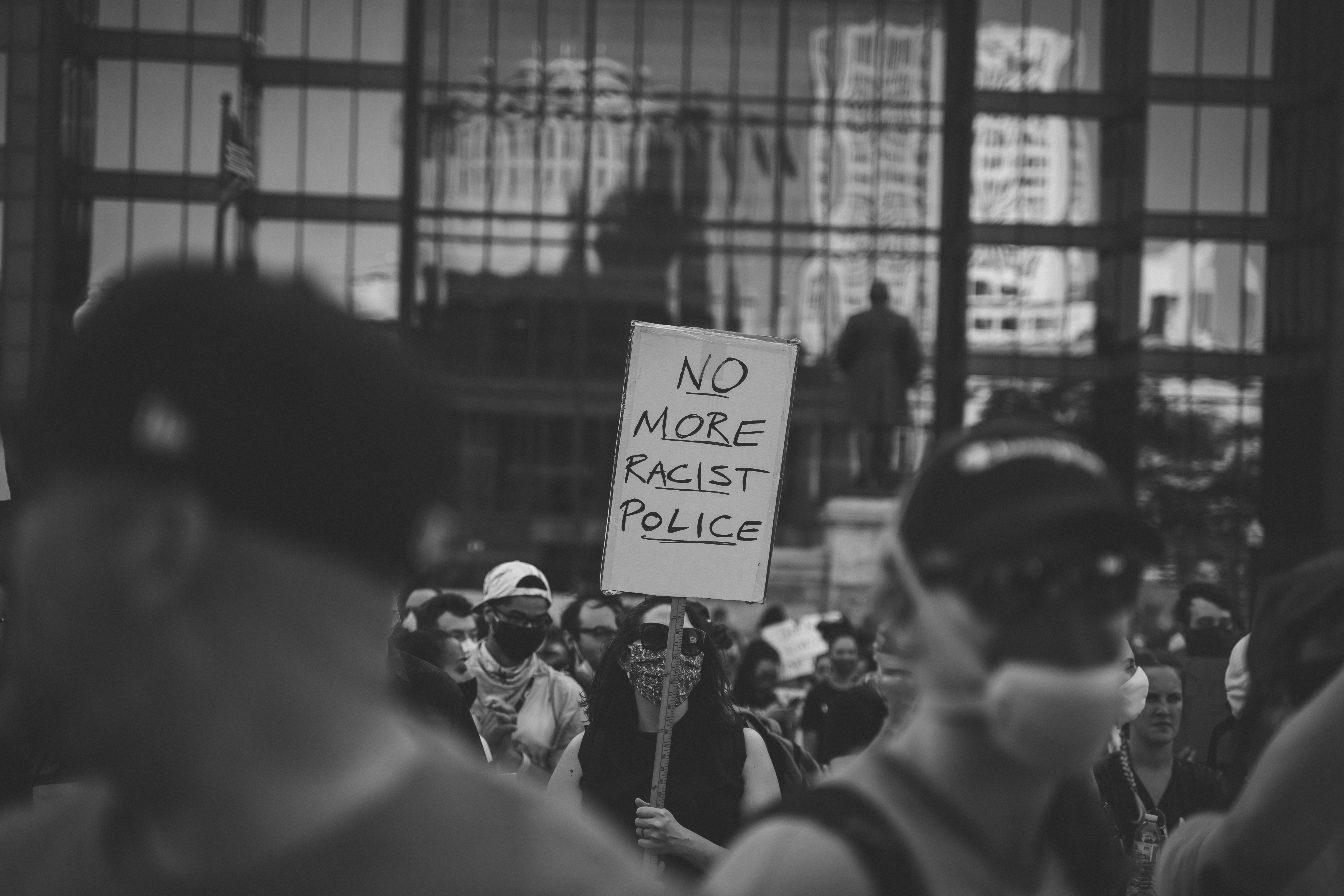 "A black and white photo. The image focuses on the middle ground featuring a protester carrying a sign that says ""no more racist police."" The foreground shows more protestors out of focus. The background shows a building with windows that reflect images of many buildings in downtown Columbus."