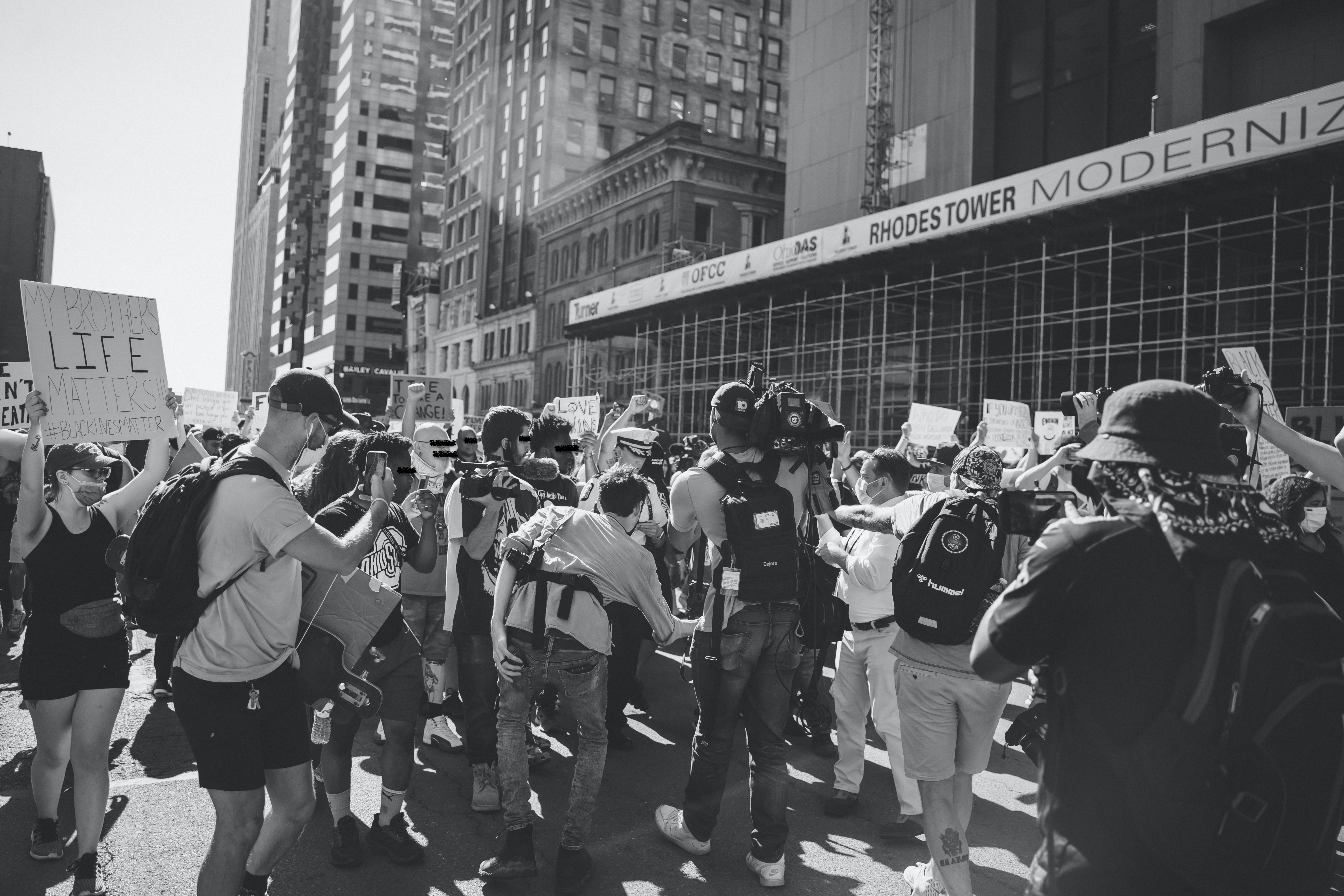 A black and white photograph. The bottom middle half of the image has a group of protestors with camera equipment and surrounding a police officer. BLM protesters with signs encircle the protestors with cameras. The top half of the image shows buildings in downtown Columbus.