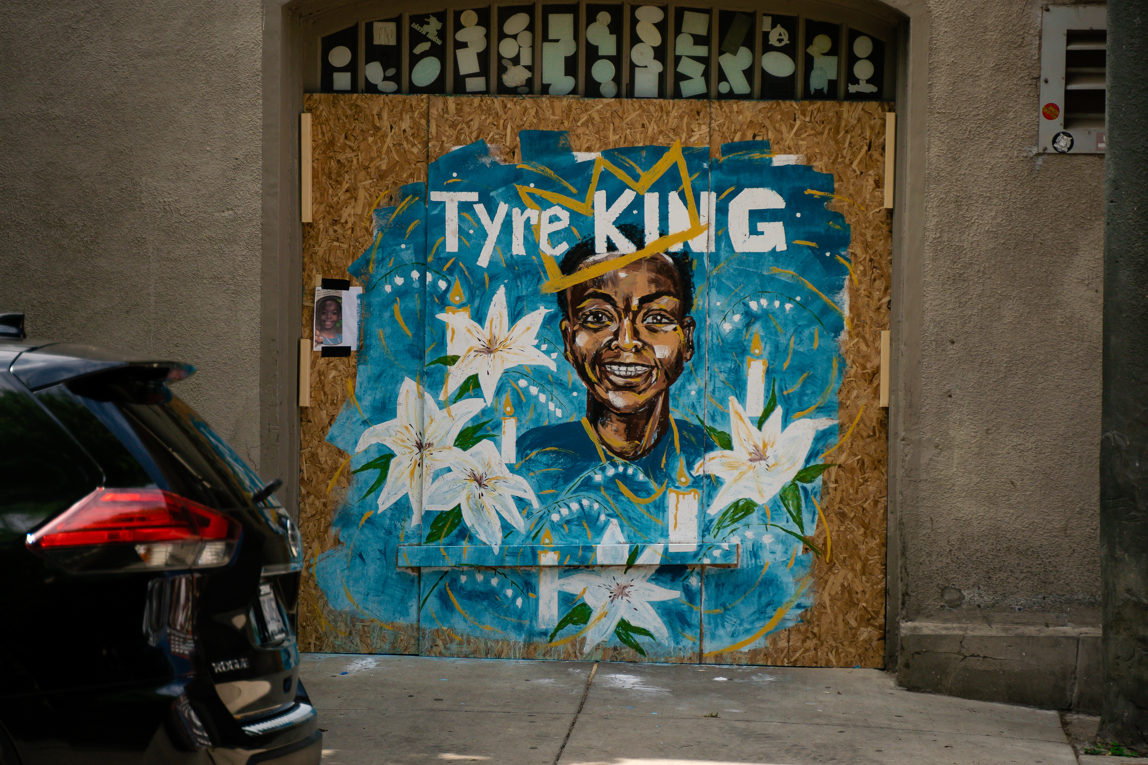 "Street Art in Downtown Columbus on plywood covering windows on a building downtown Columbus. A bright blue background is painted on the plywood featuring the painted portrait of Tyre King. He is smiling and wears a golden crown, with the text ""Tyre King"" above the portrait. Next to the portrait are painted images of white flowers, lit white candles, and golden to honor Tyre King."
