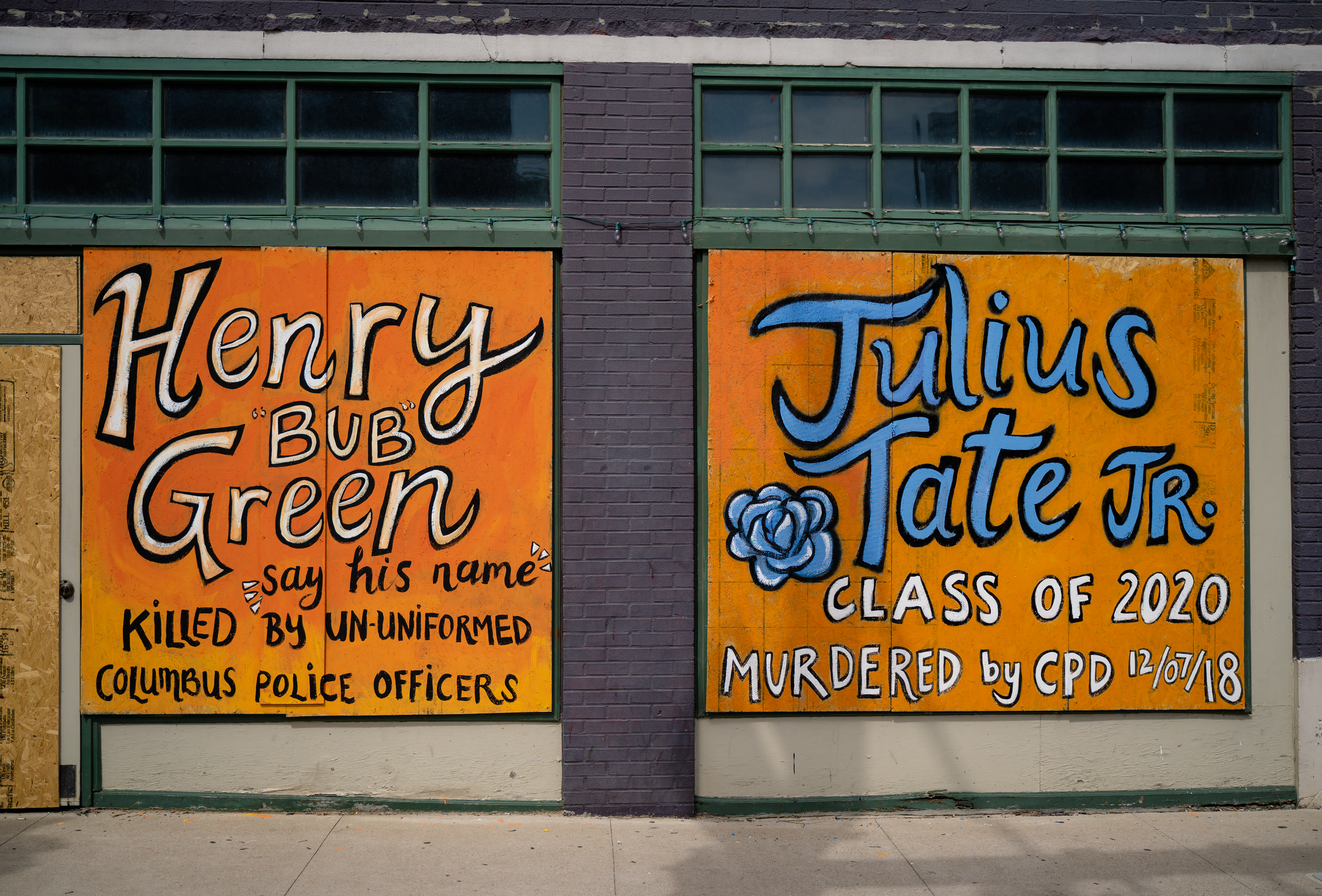 "A color image of two square pieces of street art downtown Columbus on plywood over windows. The diptych both feature bright orange backgrounds. The left one reads in blacks and white colored text, ""Henry 'Bub' Green,"" ""say his name,"" and ""killed by un-uniformed Columbus Police Officers. The right one reads in black, bright blue, and white text, ""Julius Tate Jr.,"" ""Class of 2020,"" ""murdered by CPD 12/07/18."" Next to the word ""Tate"" is a black, blue, and white painted flower."