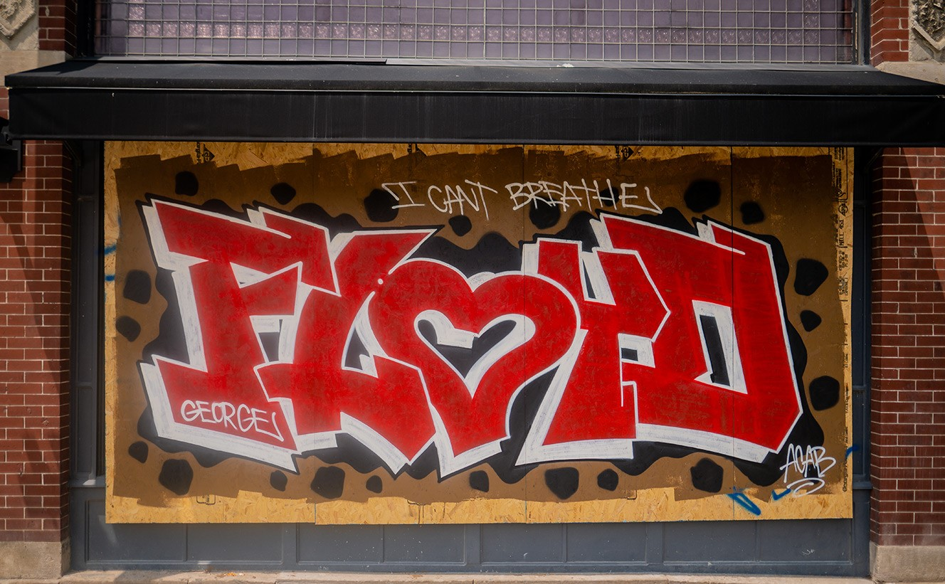 "A color photo taken from head-on. The photo shows street art on wooden boards covering windows on a brick building downtown. The biggest word is FLOYD, with the ""O"" shaped as a heart is red, with white and black drop shadows. Three smaller white text blurbs appear across the red text and reads: George; I can't breathe; ACAB. ""FLOYD"" is on a brown background with black spots."