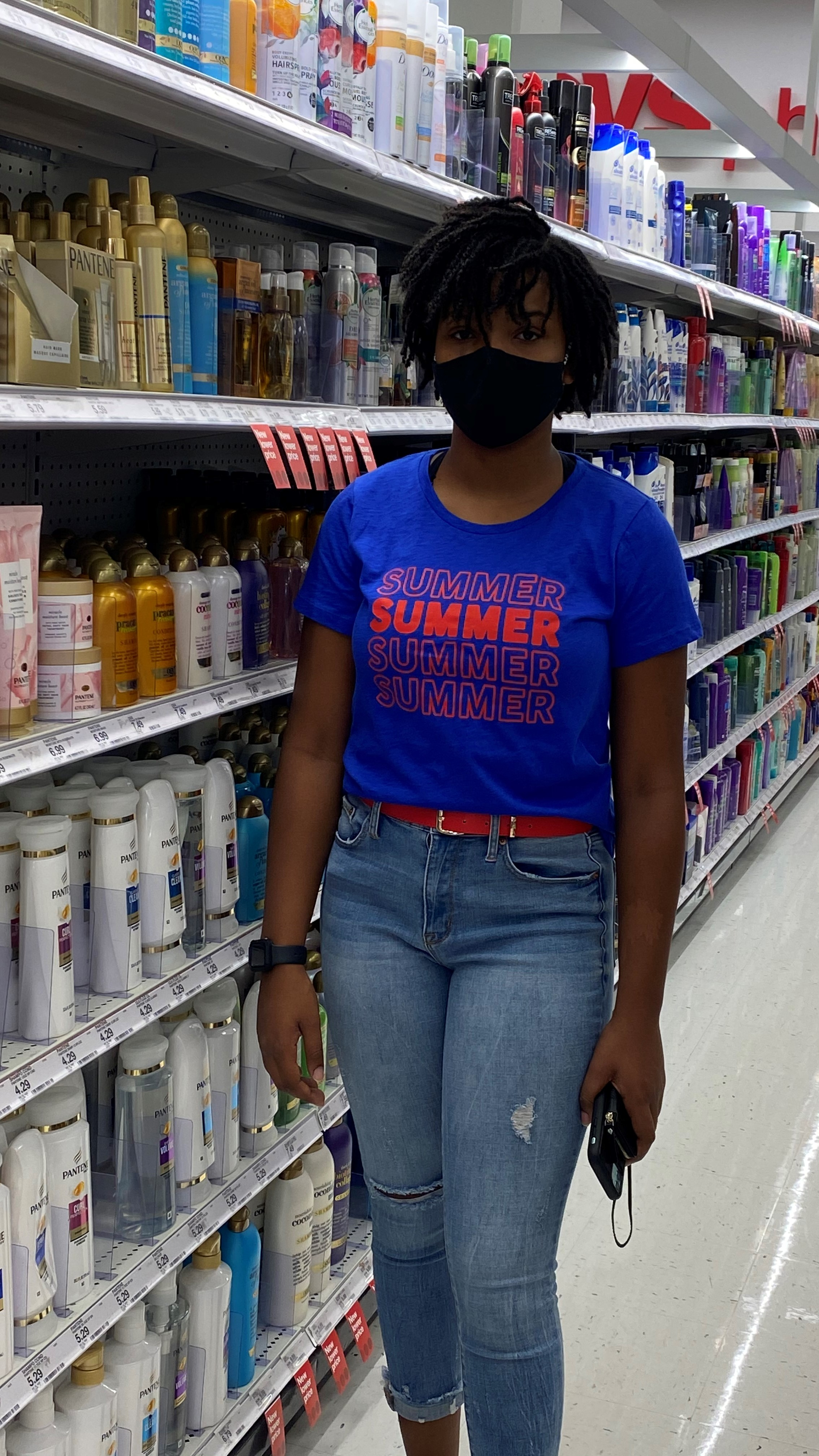 black woman standing in shampoo aisle at CVS drugstore