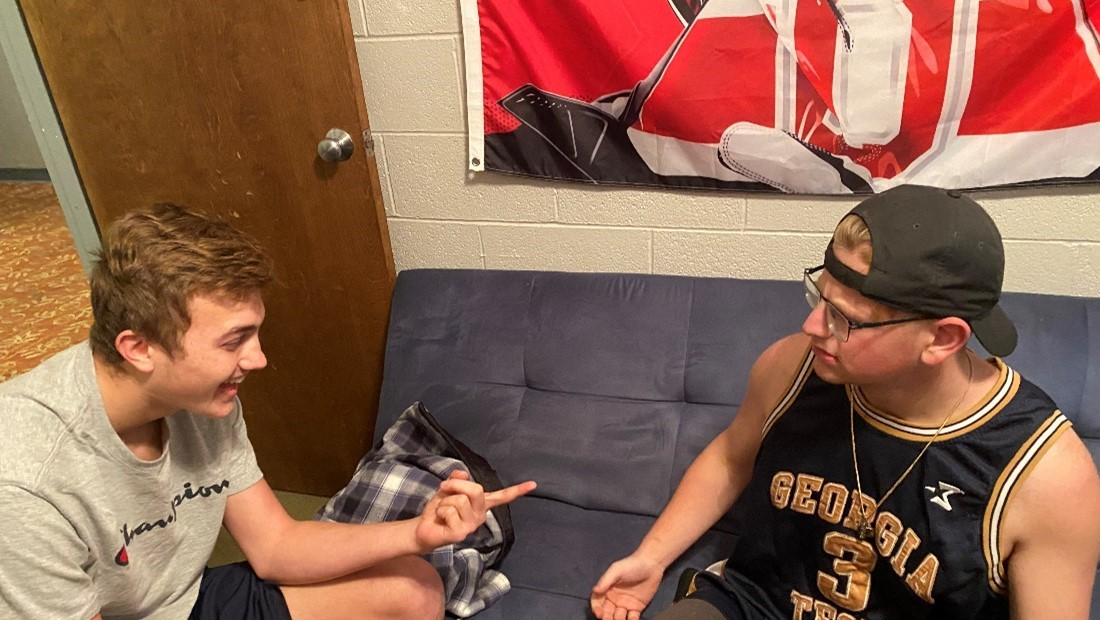 two white male college students talking in dorm room