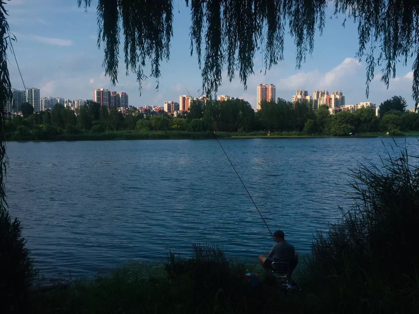 man fishing on lake with city in background