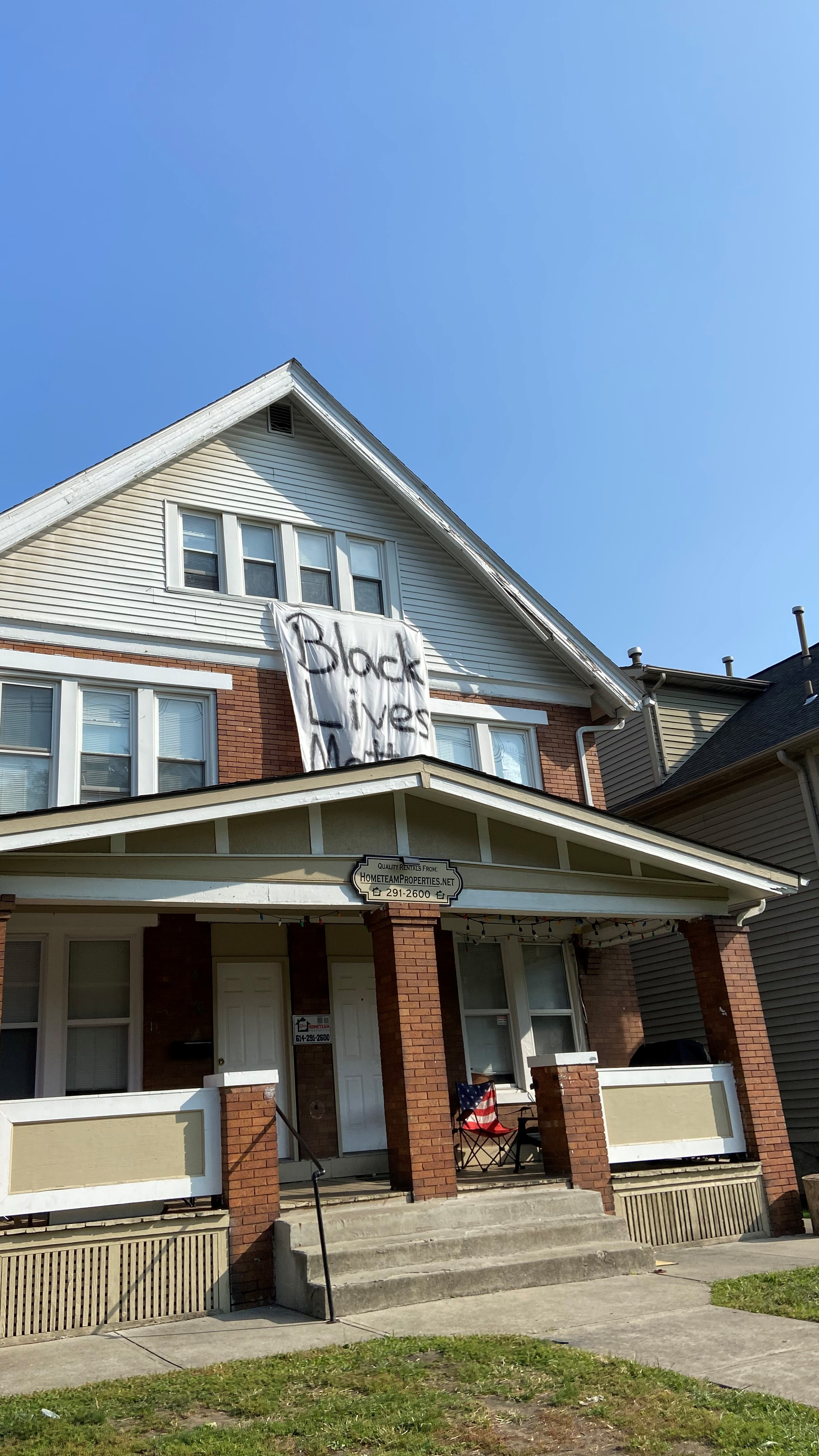 House with Black Lives Matter painted on a sheet hanging from window