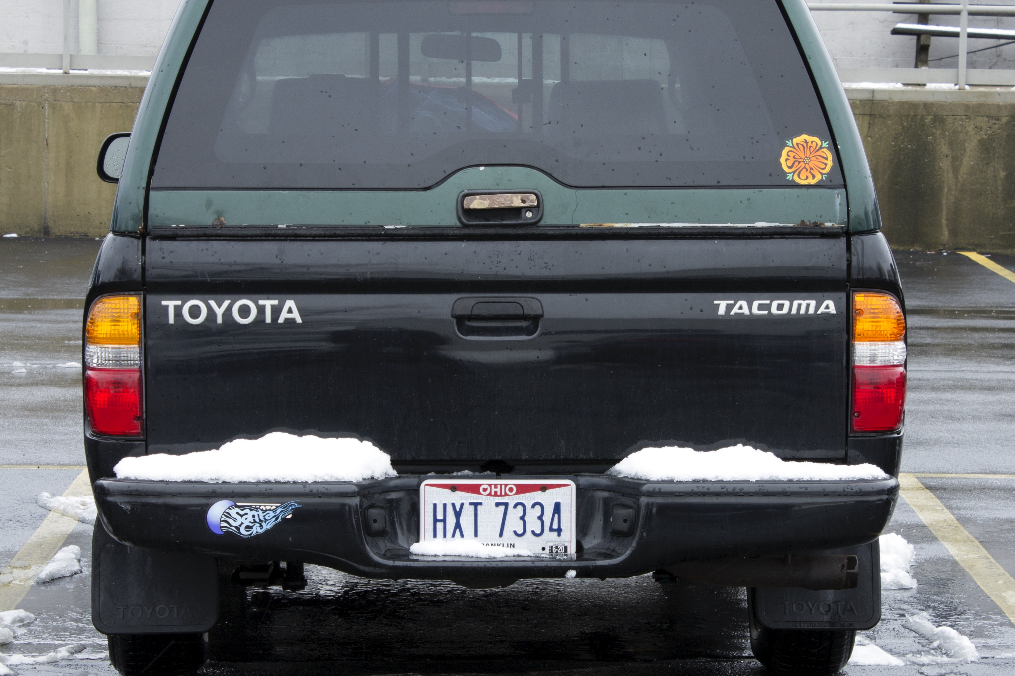 A photograph of the back end of a Toyota pick-up truck with a bed cover and a bronze tail-gate pull handle. The car is parked in a parking lot and snow sits in small piles on both the left and right sides of the bumper. The license plate reads, HXT 7334. A small, red and yellow, circular sticker is on the back window of the truck bed cover.
