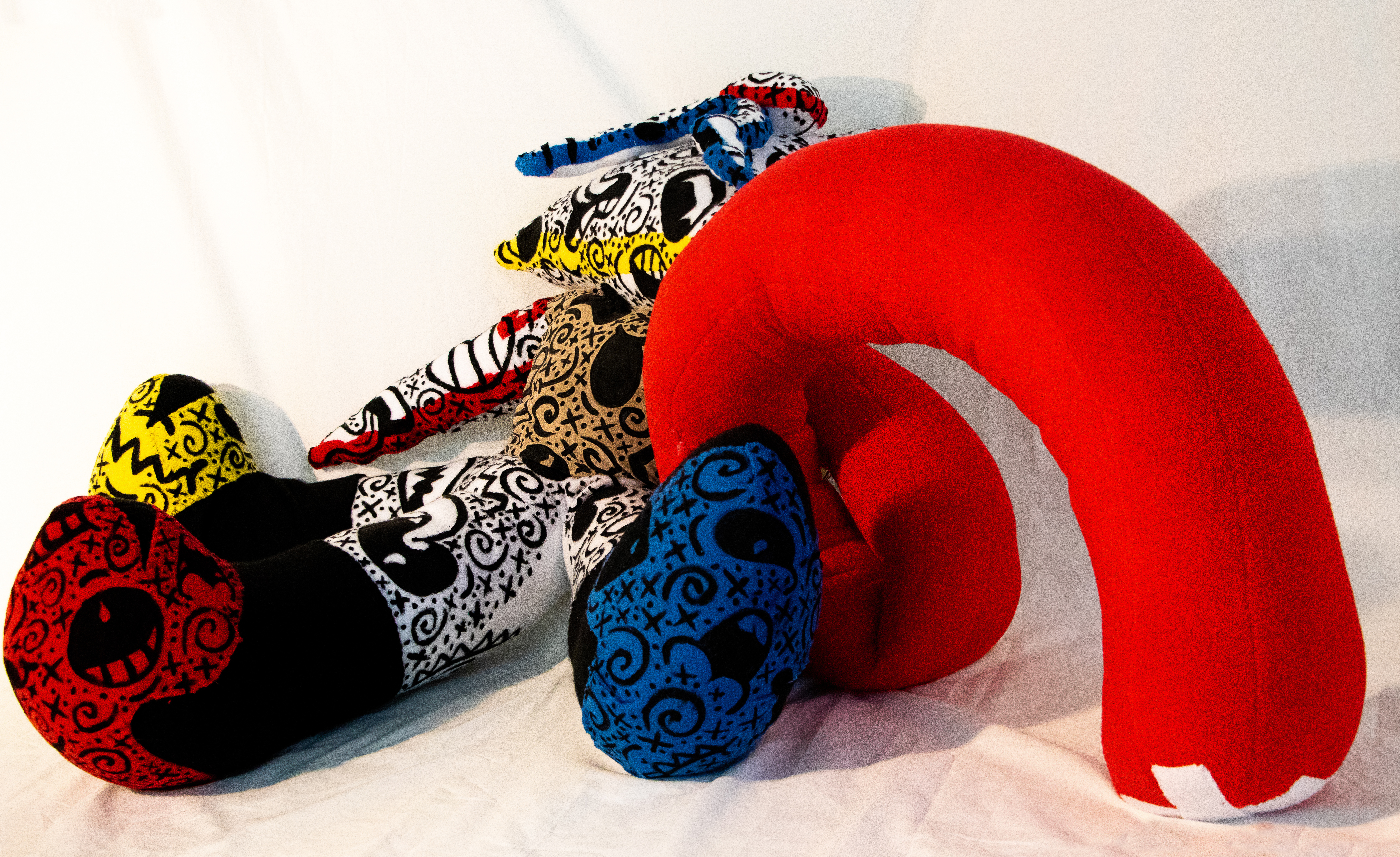 A photograph of a fabric sculpture in bright red, yellow and blue with multiple appendages and covered with black markings. Here the solely red piece is arched from the central form.