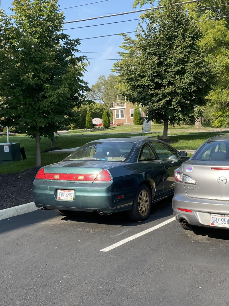 green car and silver car in parking lot