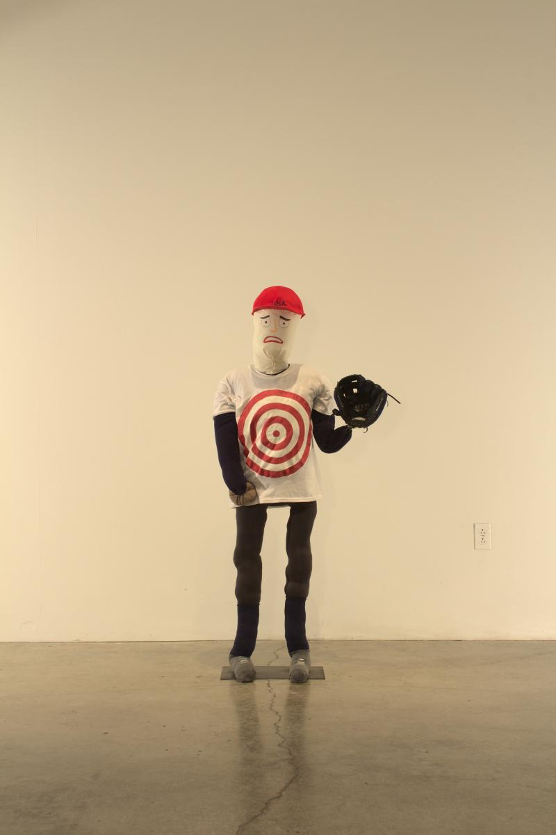Free standing mannequin holding a baseball glove raised in the left hand and wearing a t-shirt with a bulls-eye painted on the chest