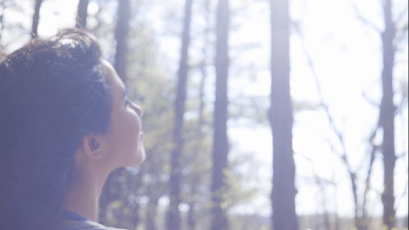 film still of a woman out in the woods facing the sunlight