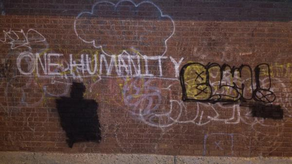 "graffiti on brick wall that states, :one humanity"" and ""BLM"""