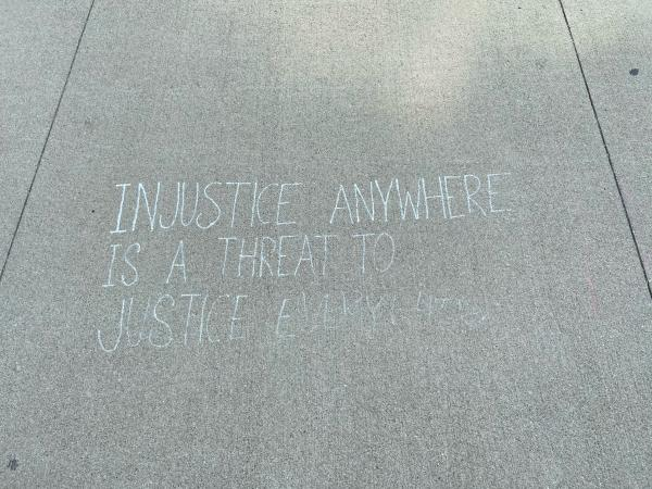 """Injustice Anywhere is a Threat to Justice Everywhere"" written in chalk on sidewalk"