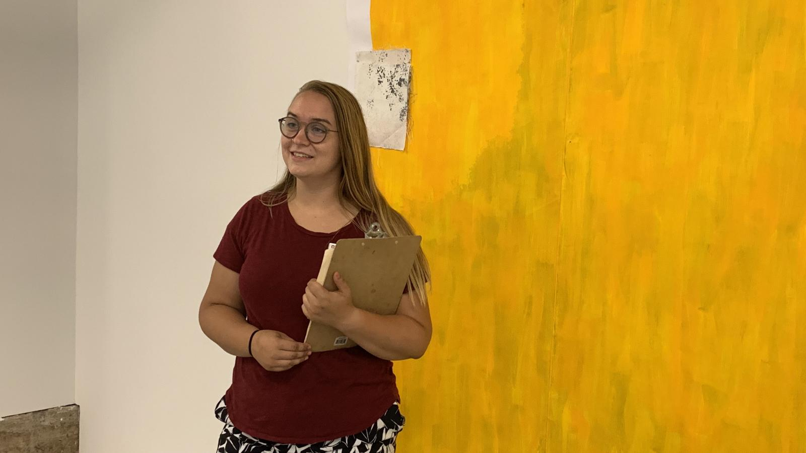 Joanna Giving a Gallery Tour in front of a Yellow Painting