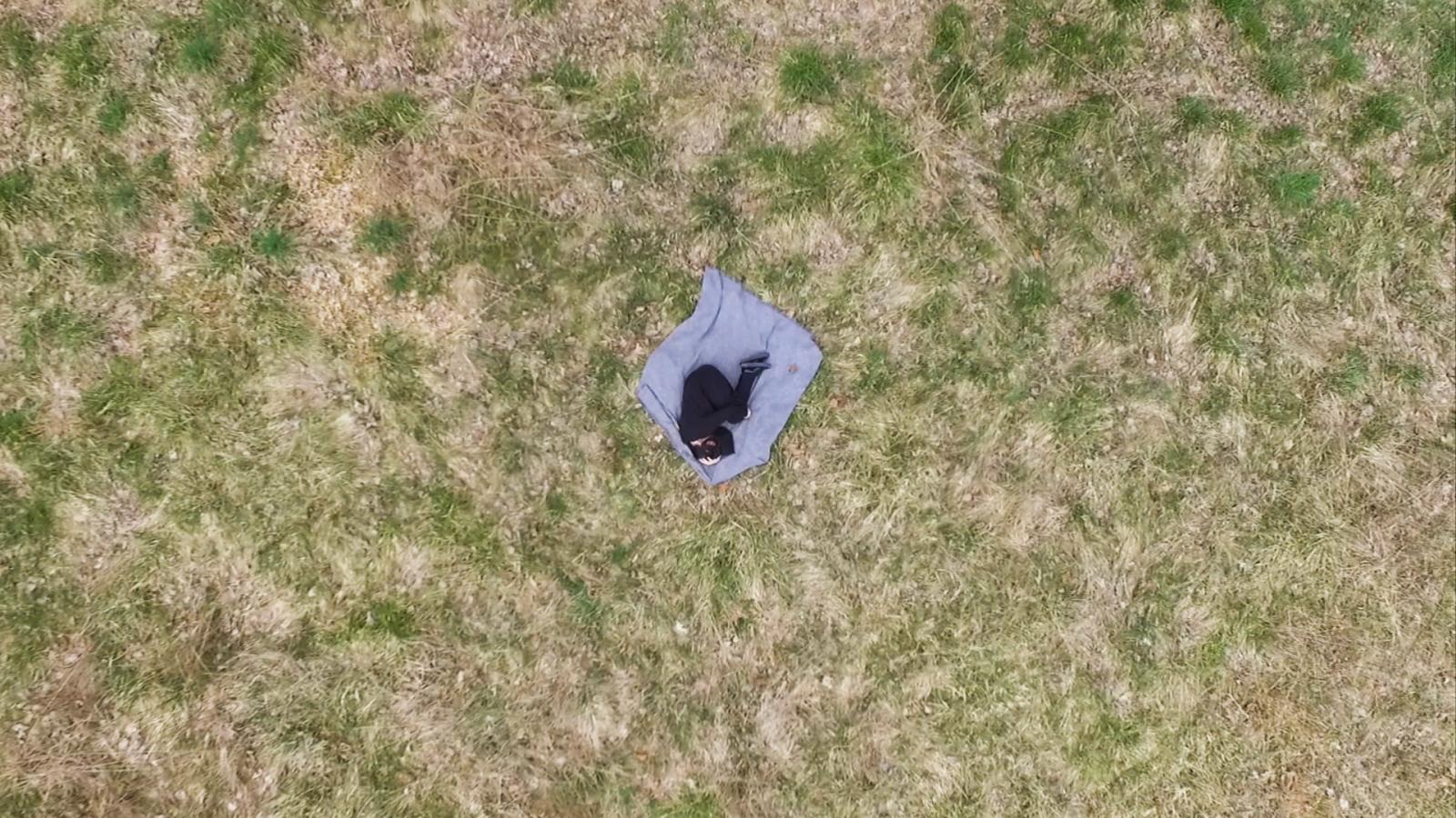 film still of an aerial shot of Person Laying on a blanket in the grass