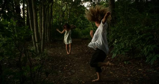 Two women dancing in a forest